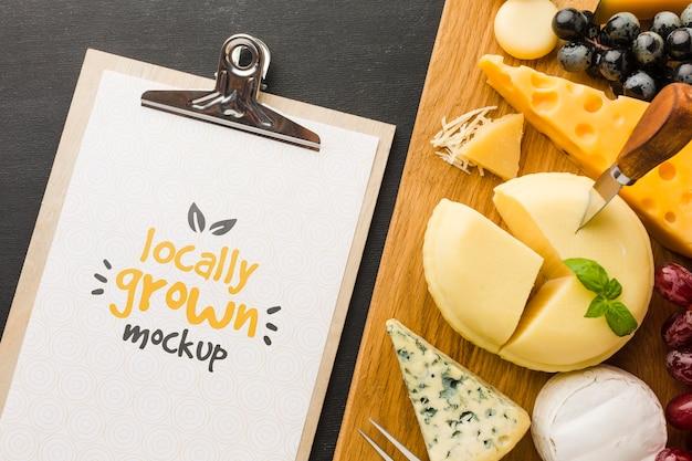 Vista dall'alto del blocco note con assortimento di mock-up di formaggi coltivati localmente