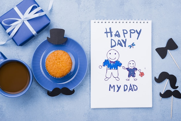 Top view of notepad with gift and cupcake for fathers day