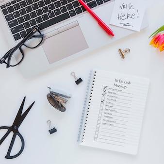 机の上のノートが付いている平面図のメモ帳