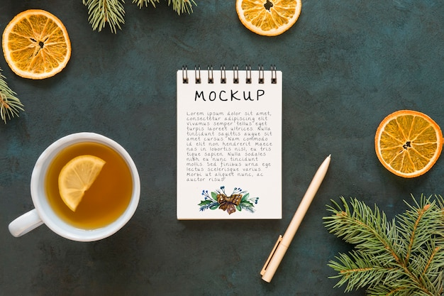 Top view of notepad with spruce branches and tea