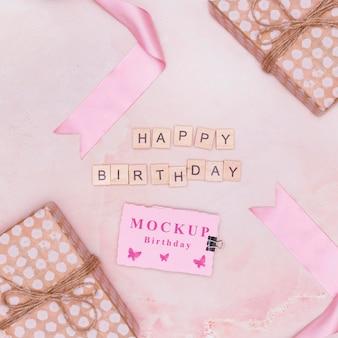 Вид сверху макета подарков на день рождения с открыткой и поздравлением
