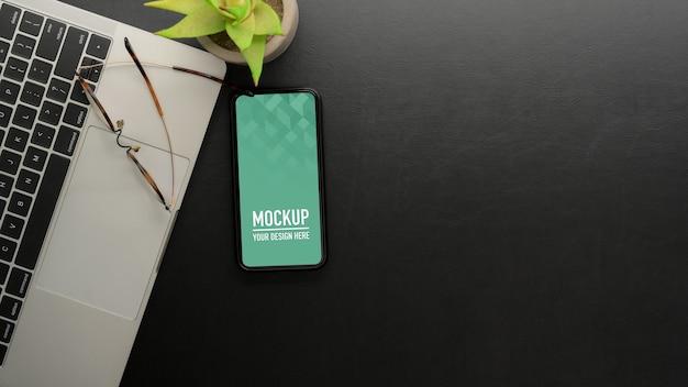 モックアップスマートフォン、ラップトップ、メガネ、コピースペースと黒いテーブルの上面図