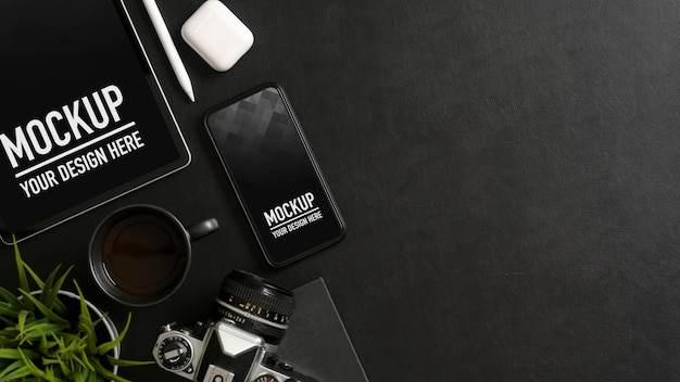 Вид сверху на черный стол с макетом смартфона, планшета, принадлежностей, аксессуаров и копией пространства