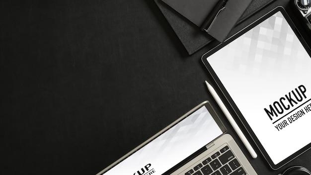 Вид сверху на черный стол с макетом планшета, смартфона, ноутбуков и копией пространства