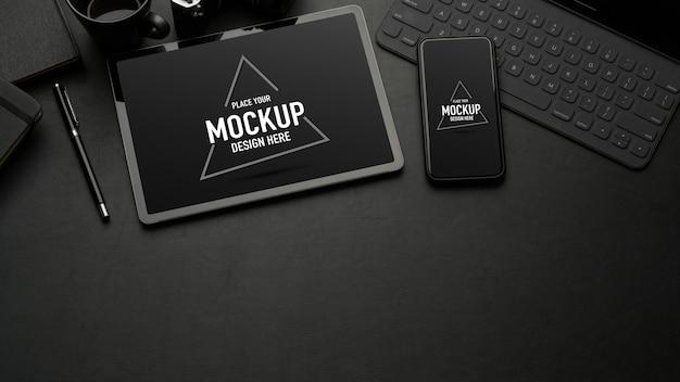 モックアップタブレット、スマートフォン、事務用品、コピースペースと黒いテーブルの上面図