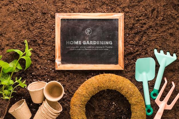 Вид сверху доски на почве с растениями и инструментами