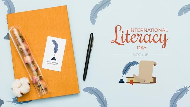 Вид сверху книги с ручкой и цветами
