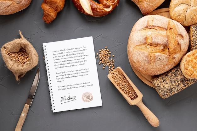 Вид сверху хлеба с пшеницей и блокнотом
