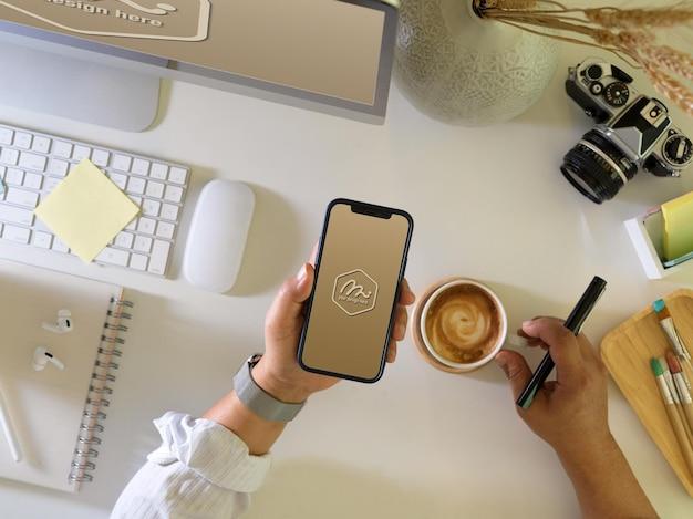スマートフォンのモックアップを保持しているビジネスマンの上面図