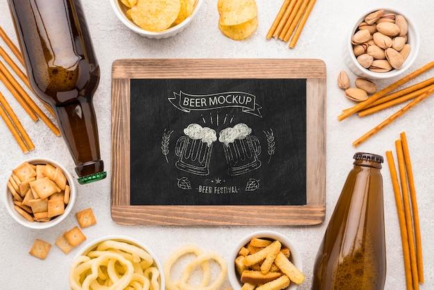맥주 병 및 간식의 구색이있는 칠판의 상위 뷰