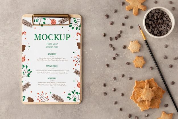 スノーフレーククッキーとチョコレートチップを使用したクリップボードの上面図