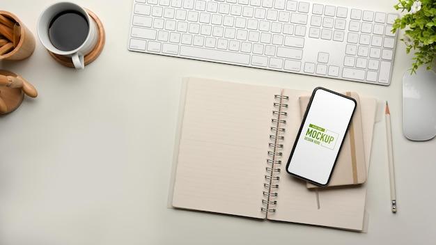 キーボードのスマートフォンの文房具とコーヒーカップとコンピュータデスクの上面図
