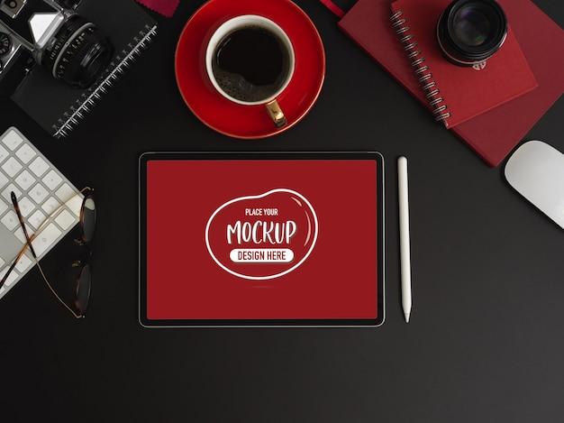 Вид сверху темного роскошного рабочего пространства с макетом планшета с чашкой кофе и канцелярскими принадлежностями