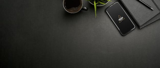 スマートフォンのモックアップ、文房具、カップと暗いワークスペースの上面図