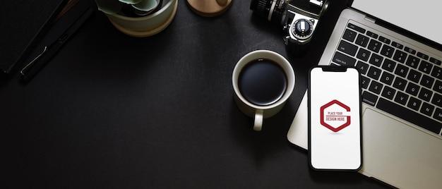 スマートフォンのモックアップと暗いワークスペースの上面図