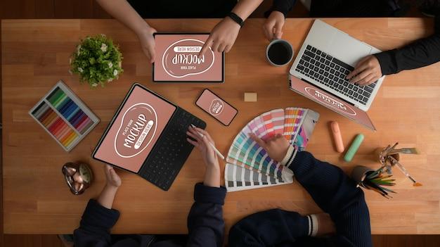 Вид сверху на брифинг команды дизайнеров по их проекту с макетами устройств