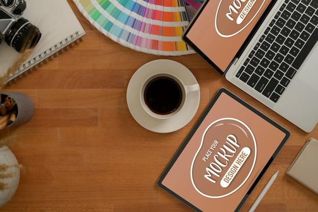 タブレット、ラップトップ、コーヒーカップ、消耗品を模擬したデザイナーのワークスペースの平面図