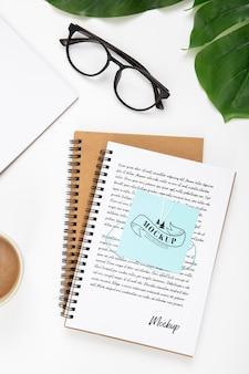 ノートと葉を持つデスク表面のトップビュー
