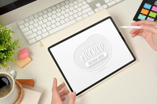디지털 태블릿을 사용하는 여성 디자이너 손의 상위 뷰
