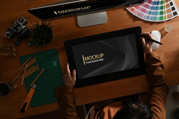 모형 디지털 태블릿으로 작업하는 여성 그래픽 디자이너의 상위 뷰