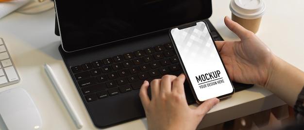 Вид сверху женской руки, держащей макет смартфона