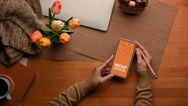 Вид сверху женской руки, использующей макет смартфона с ноутбуком и вазой для цветов