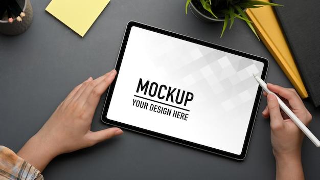 デジタルタブレットのモックアップに取り組んでいるスタイラスペンと女性の手の上面図