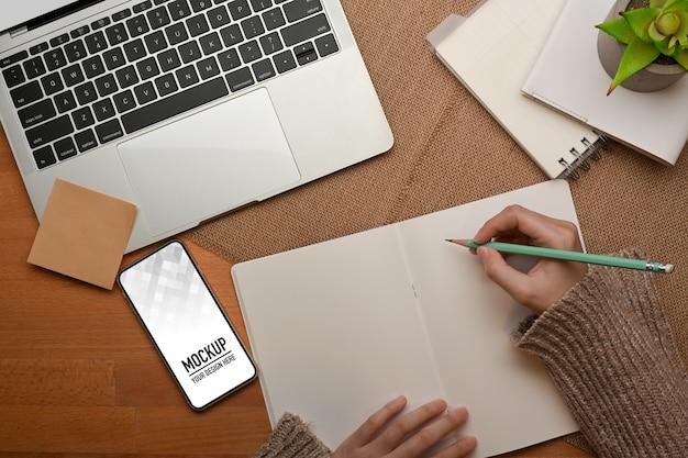 스마트 폰 모형과 작업 테이블에 빈 노트북에 쓰는 여성 손의 상위 뷰