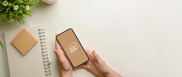 Вид сверху женских рук, держащих макет смартфона на белом рабочем месте