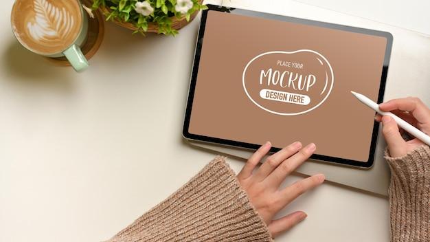 Вид сверху женских рук, использующих макет цифрового планшета со стилусом на белом столе