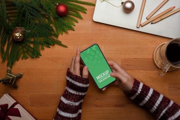 スマートフォンのモックアップを使用して女性の手の上面図