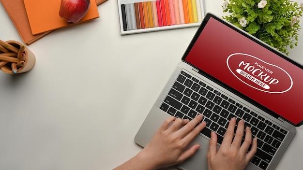 Вид сверху женских рук, работающих с макетом ноутбука
