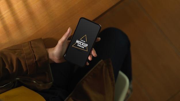 Вид сверху руки работницы, держащей макет смартфона, сидя в офисной комнате