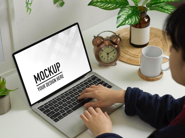 ノートパソコンのモックアップで作業している女性の上面図