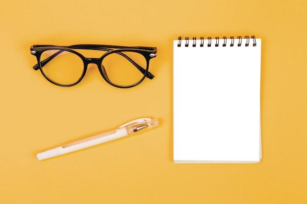 Вид сверху очки и блокнот на желтом фоне, макет, создатель сцены