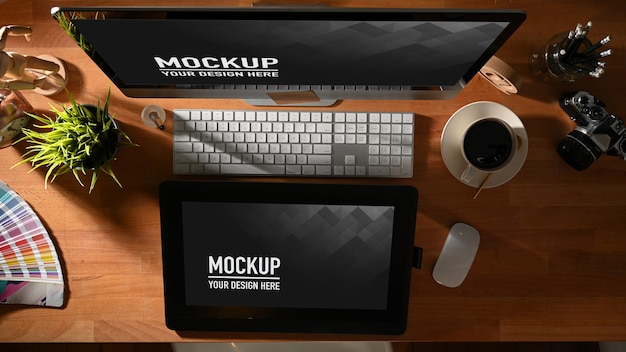 Вид сверху на рабочее пространство графического дизайнера с планшетом, компьютером и макетом принадлежностей
