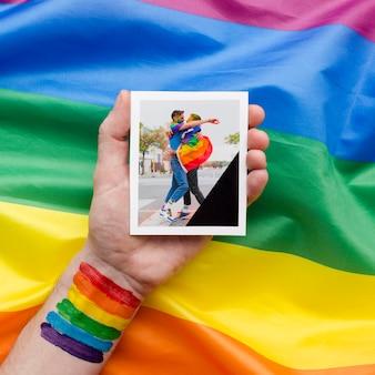 Взгляд сверху руки с радугой держа изображение для гордости