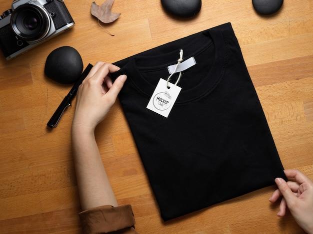 木製の机の上に値札が付いている黒いtシャツのモックアップを保持している手の上面図