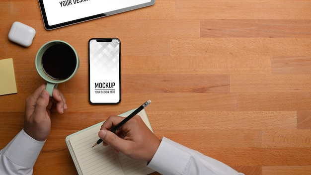 テーブルの上のタブレットとスマートフォンでオンライン学習中に鉛筆とコーヒーカップを持っている男性の手の上面図