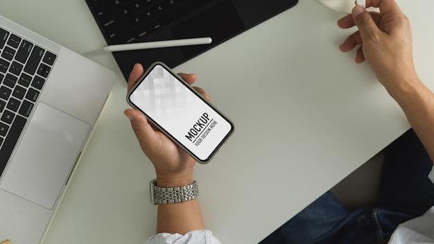 Вид сверху мужской руки, держащей смартфон, включает обтравочный контур на рабочем столе