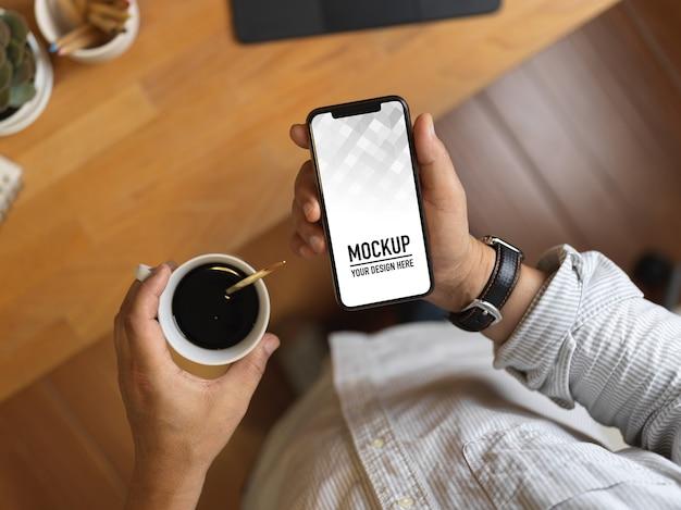 남성 손 잡고 스마트 폰 모형과 커피 컵의 상위 뷰