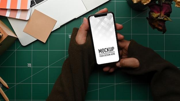 Вид сверху мужской руки, держащей макет смартфона на рабочем месте