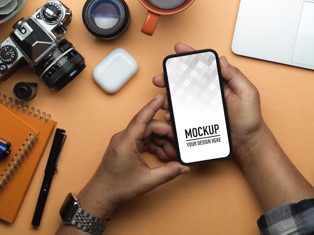 スマートフォンのモックアップを持っている男性の手の上面図