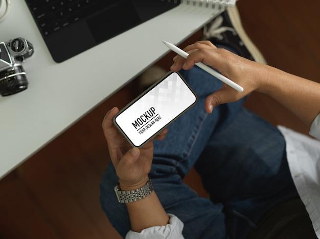 Вид сверху мужской руки, использующей горизонтальный смартфон, включая обтравочный контур, удерживая стилус