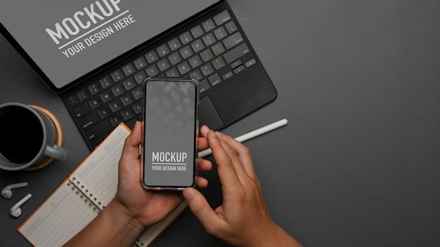 태블릿으로 작업하는 동안 스마트 폰 모형을 사용하는 남성 손의 상위 뷰