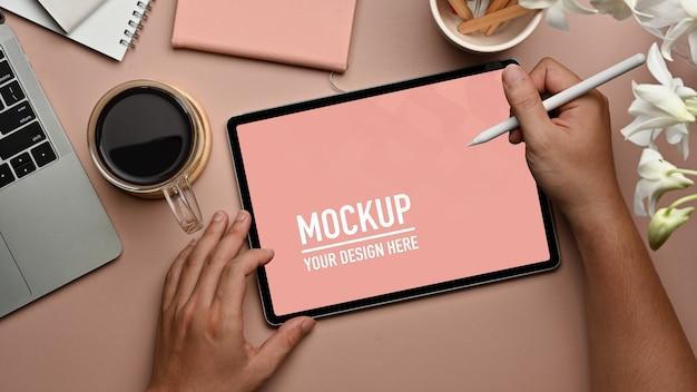 コーヒーカップと消耗品とタブレットのモックアップを使用して男性の手の上面図