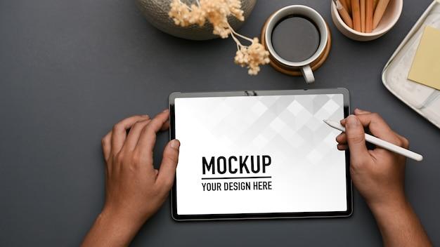 コーヒーカップ、文房具、装飾とタブレットのモックアップを使用して男性の手の上面図