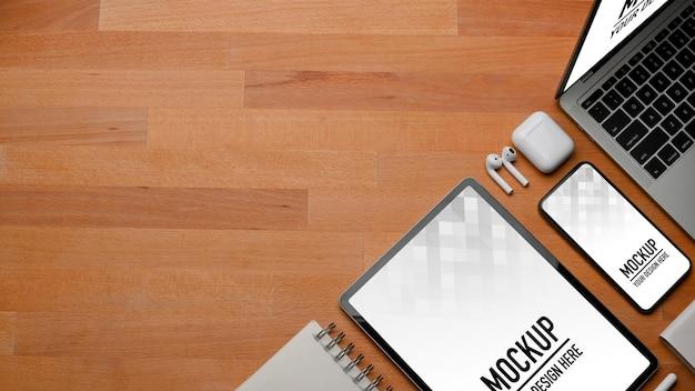 木製のテーブルにスタイラスペンでタブレットモックアップを使用して男性の手の上面図