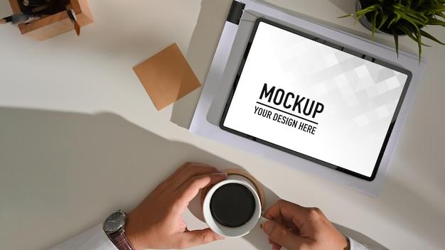 デジタルタブレットのモックアップで作業しながらコーヒーカップを保持している男性の手の上面図