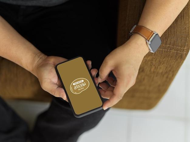 スマートフォンのモックアップを使用して男性の手の上面図